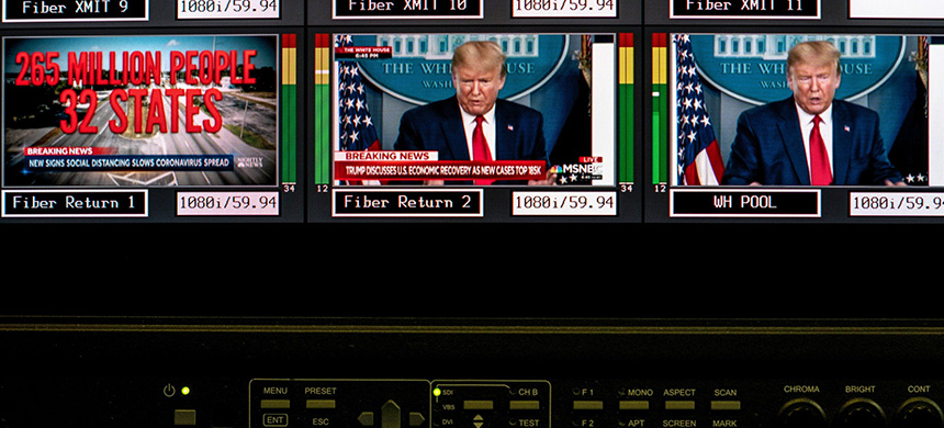 Donald Trump speaking about Covid-19 on television screens. (photo: Erin Schaff/NYT)