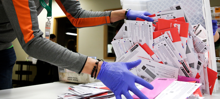 An election worker sorts vote-by-mail ballots. (photo: Jason Redmond/AFP/Getty Images)