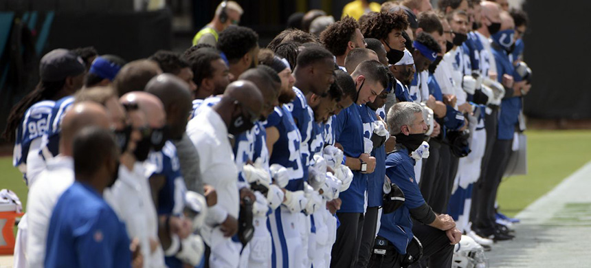 Indianapolis Colts head coach Frank Reich, center, kneels the national anthem during the first half of an NFL football game, Sunday, Sept. 13, 2020, in Jacksonville, Fla. (photo: Phelan M. Ebenhack/AP)