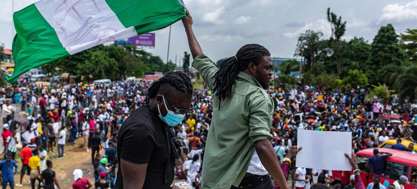 A man waves a Nigerian flag at a protest against police brutality. (photo: Benson Ibeabuchi/Getty Images)