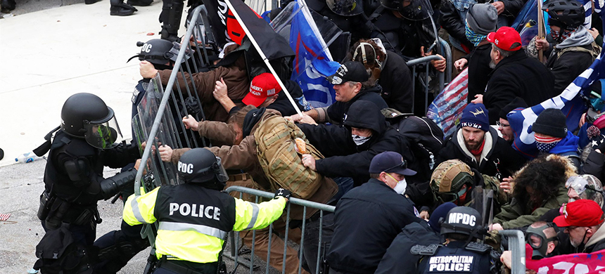 Pro-Trump rioters tear down a barricade as they clash with Capitol police on Jan. 6, 2021. (photo: Shannon Stapleton/Reuters)