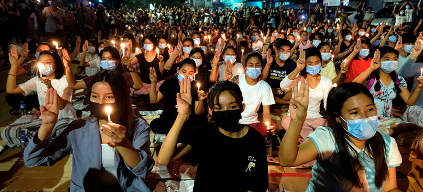 Anti-coup protesters flash the three-fingered salute during a candlelight night rally in Yangon, Myanmar, March 14th, 2021. (photo: AP)