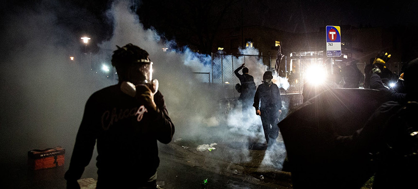 Protesters walk through clouds of tear gas as police attempt to disperse the crowd after a 7 p.m. curfew in Brooklyn Center, Minnesota, on Monday. (photo: Evan Frost/MPR News)